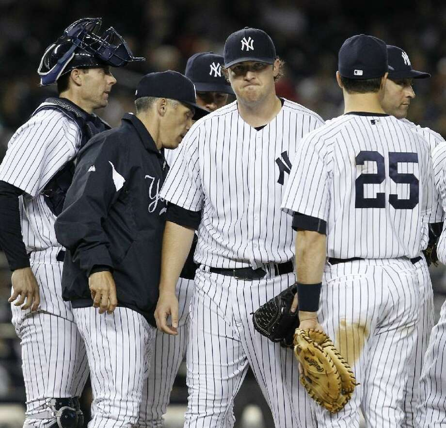 ASSOCIATED PRESS New York Yankees starting pitcher Phil Hughes, center, reacts as he leaves the mound in the sixth inning after manager Joe Girardi, second from left, took Hughes out during the Yankees' 7-1 loss to the Baltimore Orioles on Tuesday night at Yankee Stadium in New York. Yankees catcher Chris Stewart, left, third baseman Alex Rodriguez, first baseman Mark Teixeira (25) and shortstop Derek Jeter joined Hughes on the mound.