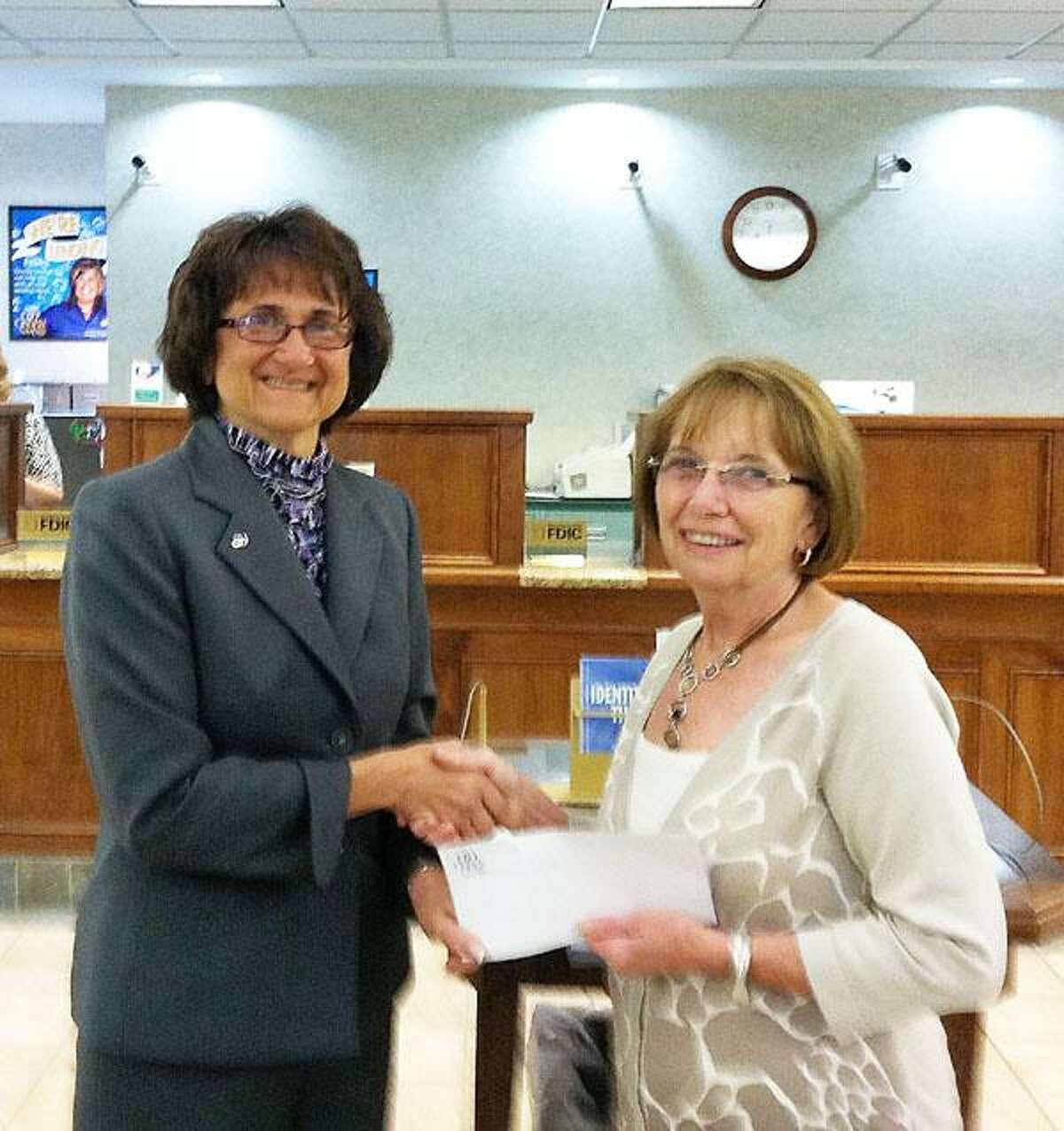 Photo Courtesy ONEIDA SAVINGS BANK Diane Karan, vice president and regional lender at Oneida Savings Bank, gives a donation to Judy Parker, tax program coordinator, RSVP of Madison County.