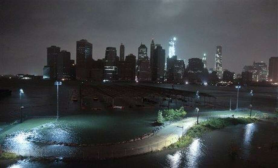 Lower Manhattan goes dark during hurricane Sandy, on Monday, Oct. 29, 2012, as seen from Brooklyn, N.Y. Sandy continued on its path Monday, as the storm forced the shutdown of mass transit, schools and financial markets, sending coastal residents fleeing, and threatening a dangerous mix of high winds and soaking rain.(AP Photo/Bebeto Matthews) Photo: AP / AP