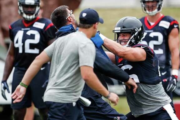 Houston Texans inside linebacker Brian Cushing (56) hits a blocking pad held by defensive coordinator Mike Vrabel during training camp at the Greenbrier on Thursday, July 27, 2017, in White Sulphur Springs, W.Va.
