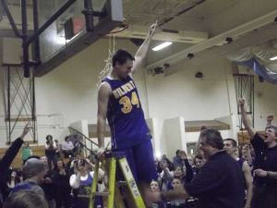 KEVIN D. ROBERTS/Register Citizen Gilbert senior center Austin Brochu celebrates with his team, coaches and fans after cutting down a piece of the net following a 93-84 overtime win over Northwestern in the Berkshire League Boys Basketball Tournament Final at Thomaston High School on Thursday night.