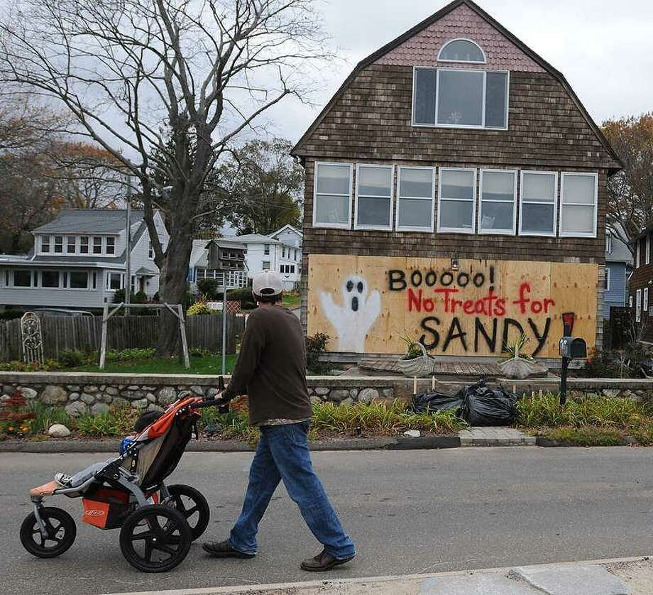 """""""BOOOOO! No Treats For SANDY"""" says a taunting message to Hurricane Sandy as a passerby walks by a boarded up house that faces directly onto Long Island Sound on Seaview Avenue and Second Avenue in Branford Sunday evening. The house, which was flooded during Tropical Storm Irene, is just separated by the road and a small beach. Photo by Peter Hvizdak / New Haven Register Photo: New Haven Register / ©Peter Hvizdak /  New Haven Register"""