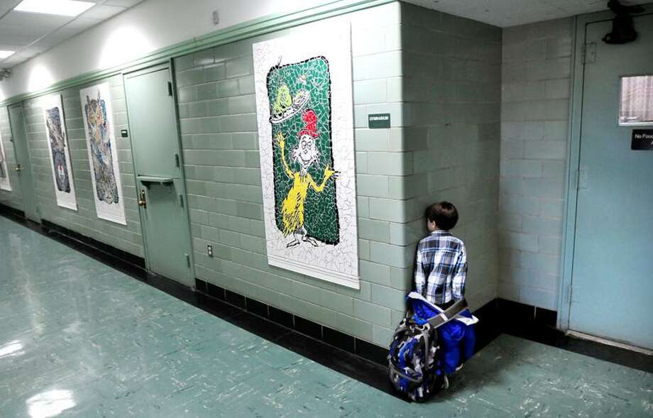 Jayden Ellison, 4, waits in the hallway of Seth Haley School in West Haven for his pre-k class to begin on 12/14/2012.  At center is a tile mosaic of Sam I Am from Dr. Seuss's Green Eggs and Ham story.Photo by Arnold Gold/New Haven Register