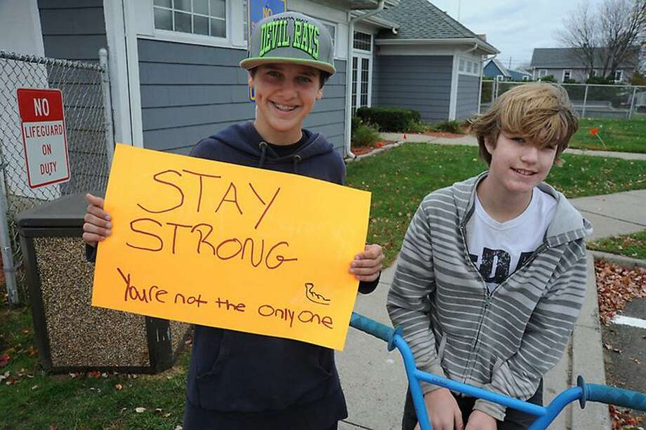 "Jake Zito and Adam Perrotti along Cosey Beach Avenue urge residents to ""stay strong."" Register photo"