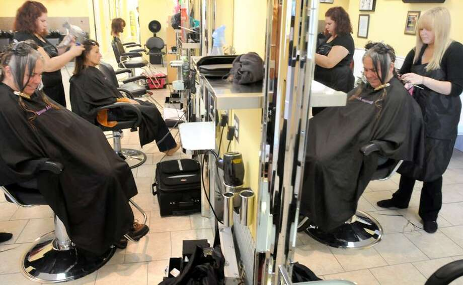 Jennifer Ward of Branford left gets her hair cut by student Darlene Diley of Clinton reflected in the mirror right while student Lizarret Dorta of New Haven left blow dries Cynthia Carlson of Branford at the Branford Academy of Hair and Cosmetology, one of the hair salons that is inspected annually by the East Shore District Health Dept. . Mara Lavitt/New Haven Register6/15/12
