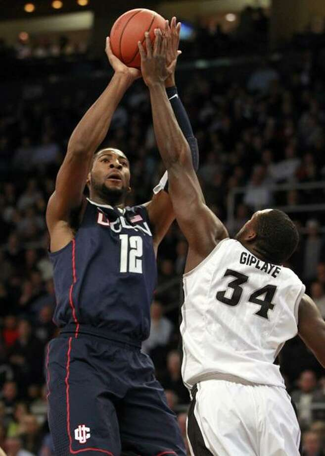 UConn's Andre Drummond (12) shoots over Providence's Ron Giplaye during the first half of Tuesday's game. (AP Photo/Steven Senne) Photo: AP / AP2012