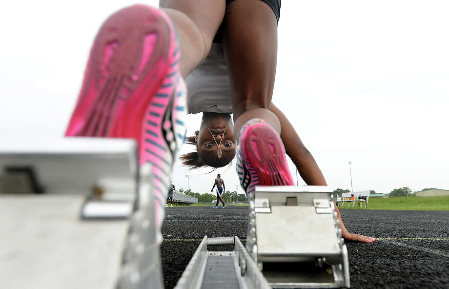 Jayla Franklin gets into position to practice taking off from the blocks as members of the Beaumont Track Club practice at Ozen High School Monday. The club, which is in its 30th year, is once again sending scores of its runners, who range in age from 6 to 18, to a state meet in McAllen this Saturday. Like many club members, Jayla is a multi-generation of family who have participated in the club. Her father Jeff Franklin, who is now a relay team coach, ran for the club as a youth. Photo taken Monday, July, 24, 2017 Kim Brent/The Enterprise Photo: Kim Brent / BEN