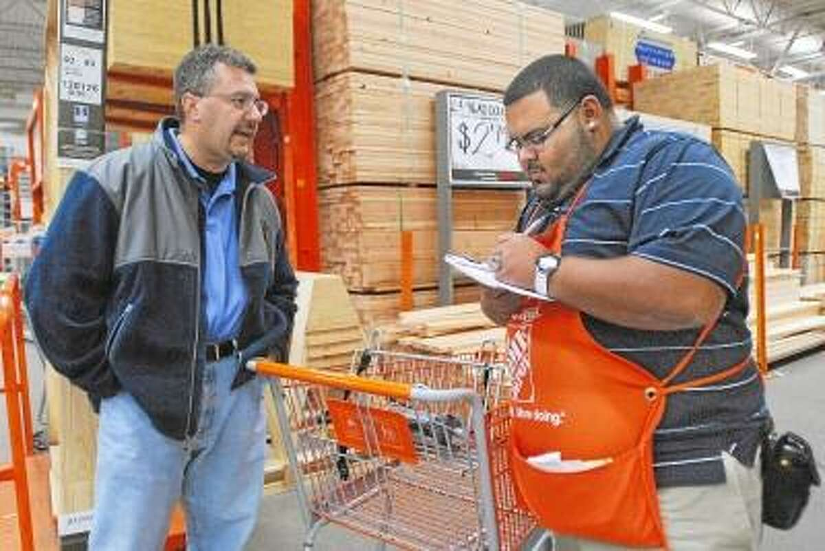Catherine Avalone/The Middletown Press Operations Manager, Manny Sanchez puts Middlefield resident Carl Pitruzzello at the top of the list for an emergency shipment of Homelite generators at the Home Depot on Washington Street in Middletown. Nine of the ten generators delivered were sold before they were unloaded off the truck in anticipation of the expected storm.