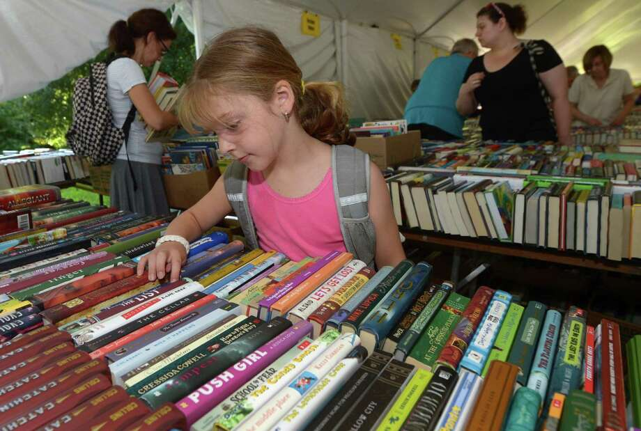 Fairfield resident Julia Fekete, 7, shops for books during the Pequot Library's 57th annual Summer Book Sale on July 21 in Fairfield. The book sale continues through Tuesday and offers over 140,000 books as well as CDs and records, and proceeds from the sale directly fund Pequot Library's programs, library services and events. Photo: Erik Trautmann / Hearst Connecticut Media / Norwalk Hour