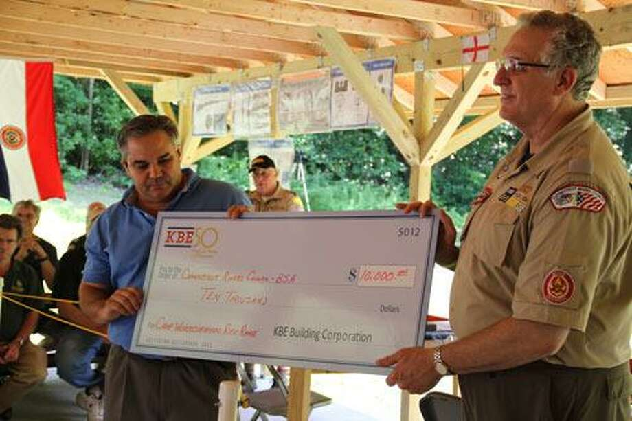 Mike Kolakowski, President and CEO of KBE Building Corporation, and Steven Smith, Scout Executive and CEO of the Connecticut Rivers Council pose with KBE's financial contribution to the Camp Workcoeman's new rifle range.