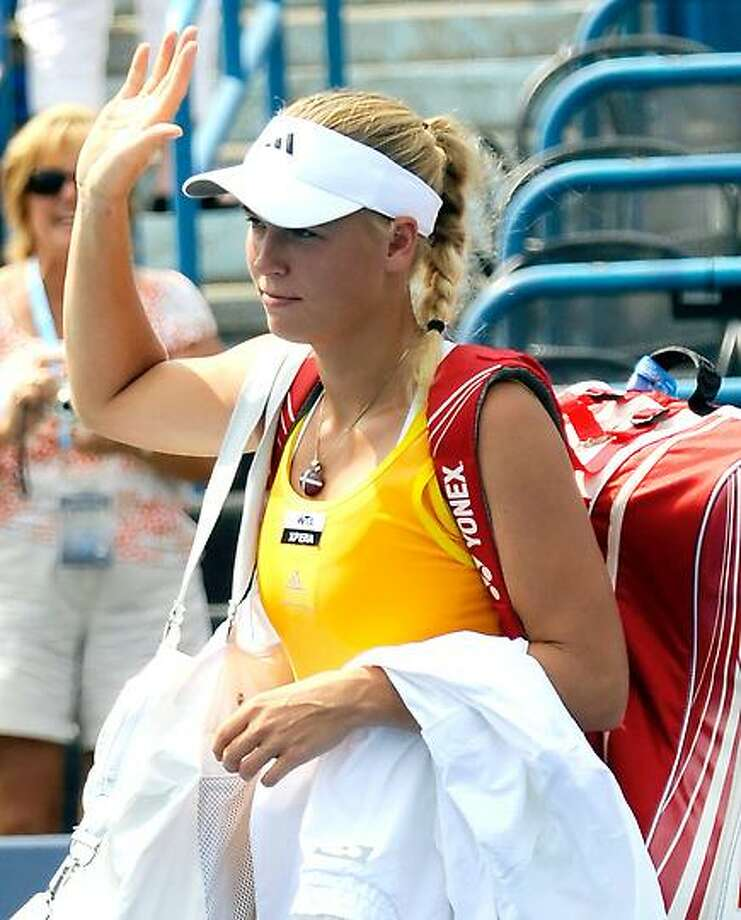 Caroline Wozniacki waves to the fans as she leaves Stadium Court after she had to retire from her  semifinal match with Maria Kirilenko Friday at the New Haven Open. (Bob Child/Special to the Register) Photo: New Haven Register / Bob Child
