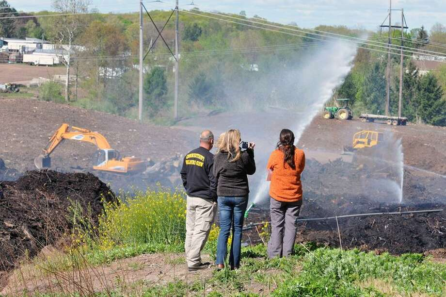 North Haven-- DEEP officials look over the fire at Borrelli Farm in North Haven that has been burning since April 10th. Photo- Peter Casolino/New Haven Register 04/27/12