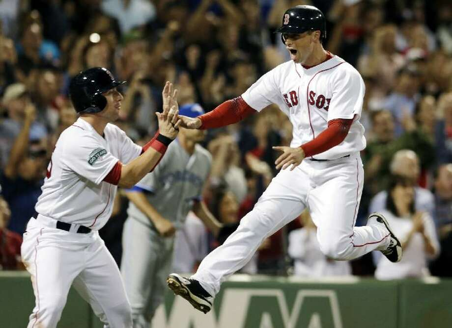 ASSOCIATED PRESS Boston Red Sox's Daniel Nava, right, jumps as he celebrates with Ryan Kalish after they scored on Dustin Pedroia's single in the seventh inning of Tuesday's game against the Toronto Blue Jays at Fenway Park in Boston. The Red Sox won 5-1.