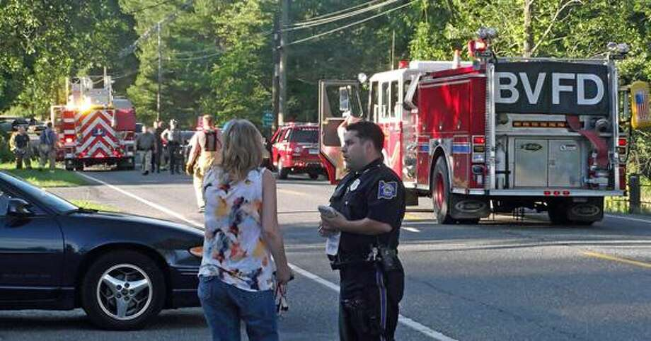 A Torrington Police officer interviews a potential witness at the scene of Wednesday night's fatal motorcycle accident on Winsted Road. (MICHELLE MERLIN / Register Citizen)