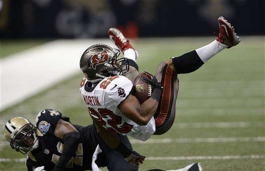New Orleans Saints strong safety Roman Harper (41) upends Tampa Bay Buccaneers running back Doug Martin (22) in the first half of an NFL football game at the Mercedes-Benz Superdome in New Orleans, Sunday, Dec. 16, 2012. (AP Photo/Bill Feig) Photo: AP / FR44286 AP