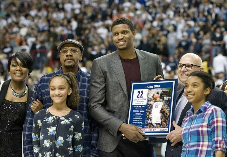 Former Connecticut player Rudy Gay, center, stands with his family and interim athletic director Paul Pendergast as his No. 22 is unveiled on the UConn Huskies of Honor wall prior to an NCAA college basketball game in Storrs, Conn., Saturday, Feb. 25, 2012.  (AP Photo/Jessica Hill) Photo: AP / AP2012