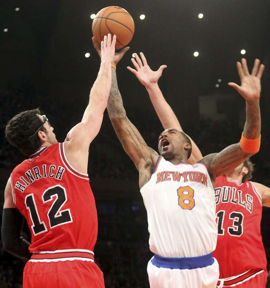 New York Knicks' J.R. Smith (8) goes to the the basket against Chicago Bulls' Kirk Hinrich (12) and Joakim Noah during the first half of an NBA basketball game on Friday, Dec. 21, 2012, at Madison Square Garden in New York.  (AP Photo/Mary Altaffer) Photo: AP / AP