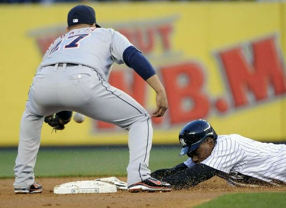 New York Yankees' Curtis Granderson, right, slides into second base with a double as shortstop Jhonny Peralta takes the throw during the first inning of a baseball game on Friday, April 27, 2012, at Yankee Stadium in New York. (AP Photo/Bill Kostroun) Photo: ASSOCIATED PRESS / AP2012