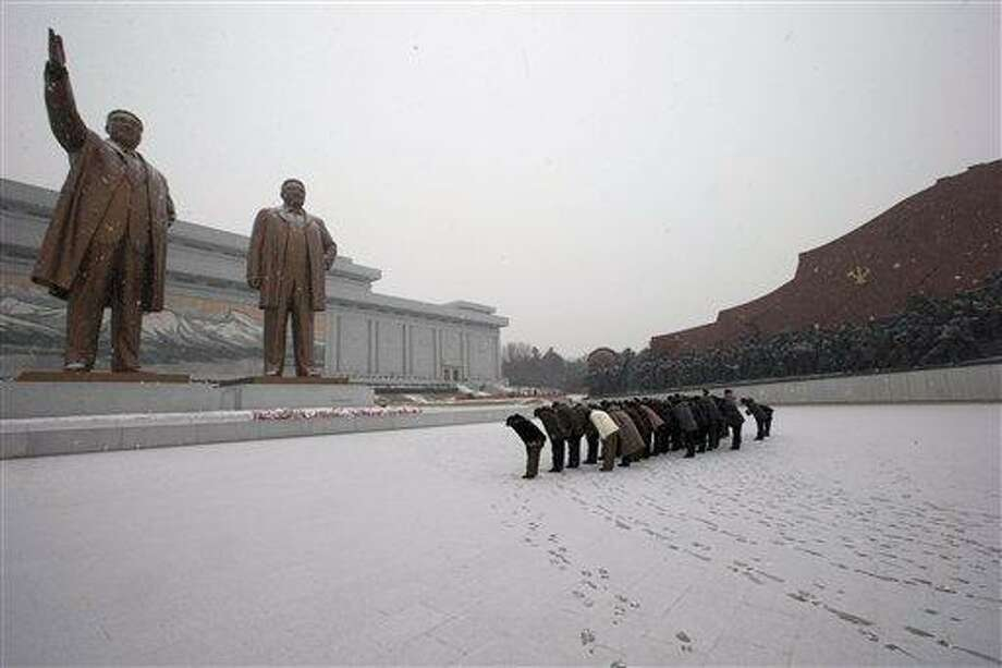North Koreans bow in front of the statues of late North Korean leaders Kim Il Sung, left, and Kim Jong Il at Mansu Hill as it snows in Pyongyang, North Korea, Friday, Dec. 21, 2012. (AP Photo/Ng Han Guan) Photo: AP / AP
