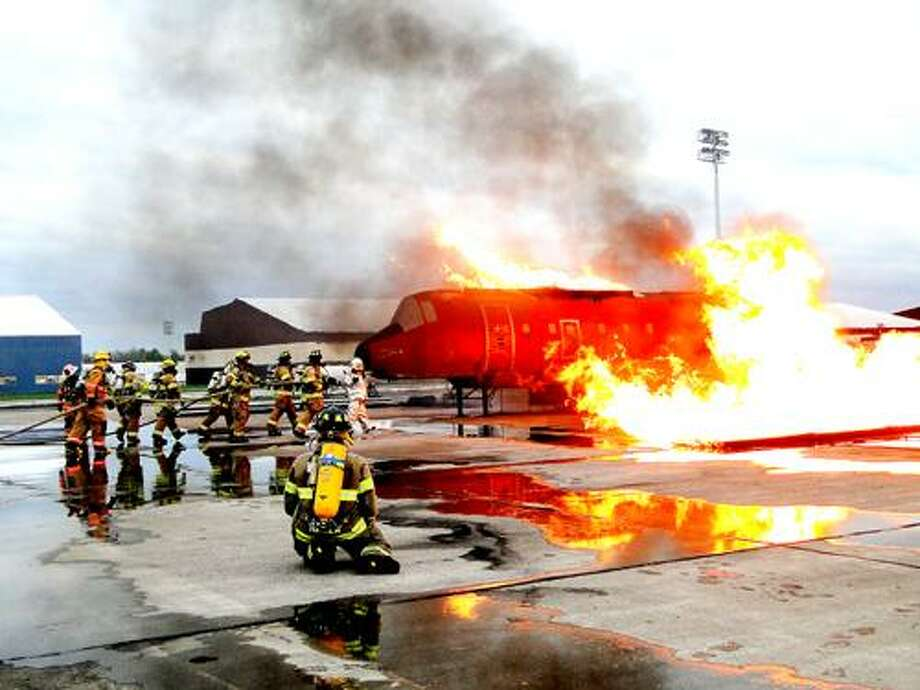 Photo Special to the Dispatch by RACHEL MURPHY Area firefighters practice dousing an aircraft fire at Griffis Airport during an aircraft fire simulation.