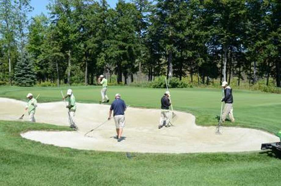 Dispatch Staff Photo by KYLE MENNIG A crew works on a bunker on Atunyote's sixth hole.