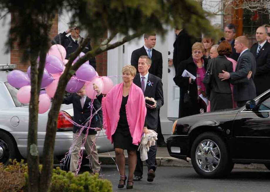 The parents of Grace McDonnell and her brother make their way outside the St. Rose of Lima Church on Church Hill Road in Newtown Friday after the funeral of their daughter. They received the pink and purple balloons to set off into the sky on her behalf. Erica Miller/Digital First Media