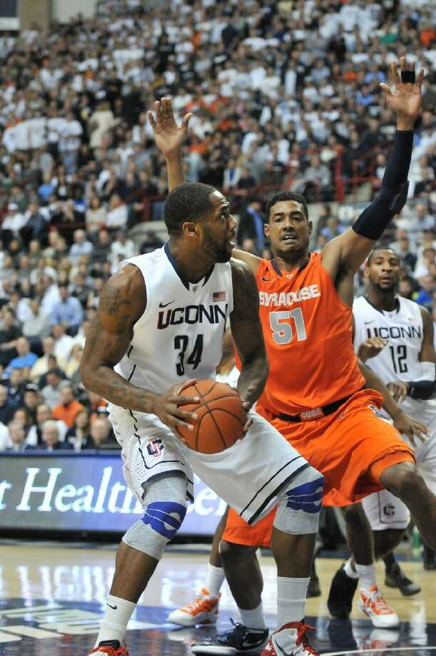 ASSOCIATED PRESS Connecticut center Alex Oriakhi is defended down low by Syracuse center Fab Melo in the first half of Saturday's game at Gampel Pavilion in Storrs.