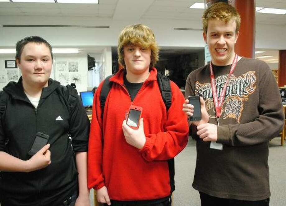 MIKE AGOGLIATI/ Register Citizen  Torrington high School students Blair Wachtel, Nick Tomchick and Zach Lange display mobile devices they hope the school board will allow them to use more often. Currently a policy allows them at the school, but forbids them to be used during the day. The three students along with Cassie Jedlinski, not pictured will make a presentation to the Board of Education's policy subcommittee this week.