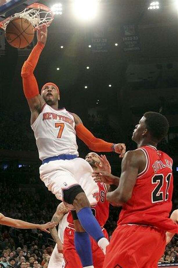 Chicago Bulls' Jimmy Butler (21) watches as New York Knicks' Carmelo Anthony scores a basket during the first half of an NBA basketball game on Friday, Dec. 21, 2012, at Madison Square Garden in New York. (AP Photo/Mary Altaffer) Photo: ASSOCIATED PRESS / AP2012