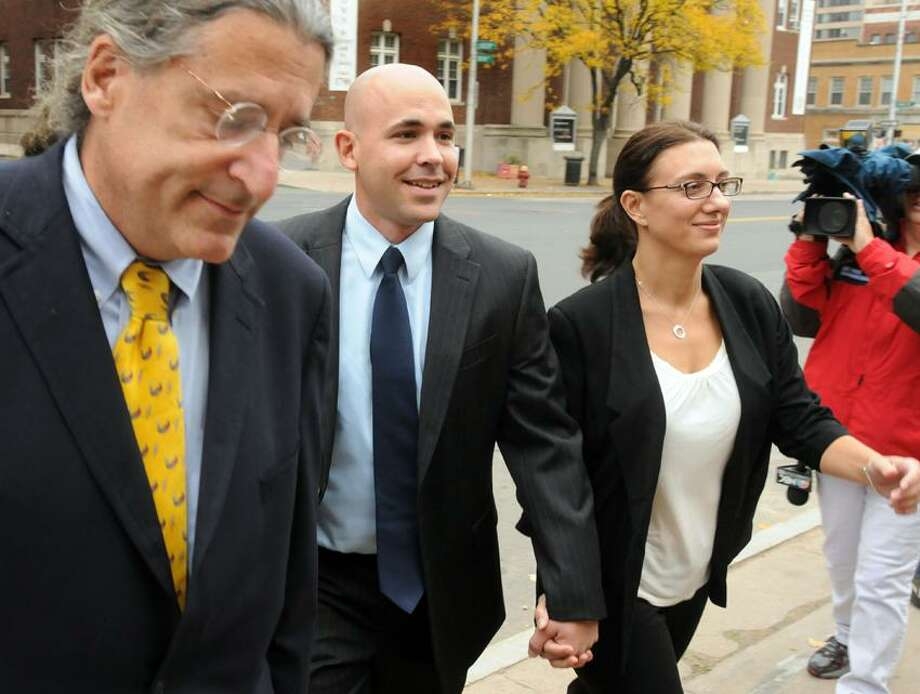 East Haven Police Officer Jason Zullo center with attorney Norman Pattis left and an unidentified woman right walks to Federal Courthouse in Hartford. Zullo was changing his not-guilty plea in the East Haven police profiling case. Mara Lavitt/New Haven Register10/23/12