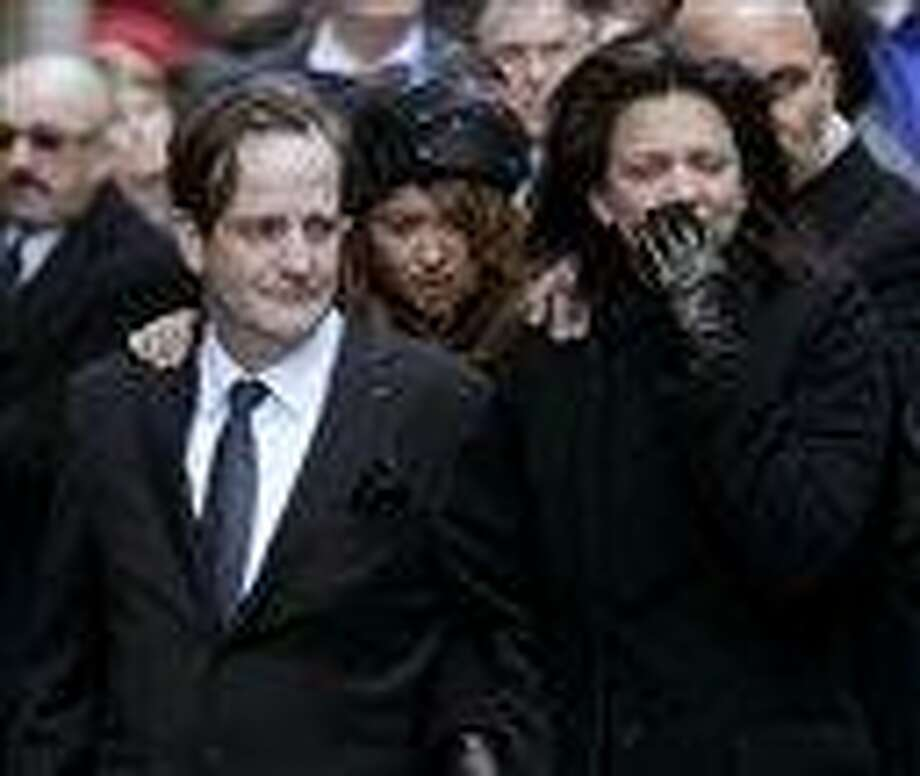 """In this Jan. 5 file photo, Matthew Badger, left, and Madonna Badger, parents of three children killed in a fire, watch as their children's caskets are carried into a church during the funeral in New York. Badger said in an interview aired Thursday on NBC's """"Today"""" show that she considered putting fireplace ashes, blamed for the Christmas Day fire, outdoors about an hour before flames swept through the home. The fire in Stamford killed 7-year-old twins Grace and Sarah Badger, 9-year-old Lily Badger, and their grandparents Lomer and Pauline Johnson. Associated Press Photo: AP / AP2012"""