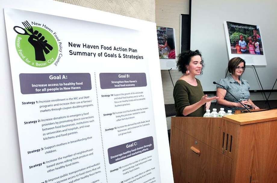 Tagan Engel, right, Chair of the New Haven Food Policy Council, and Alycia Santilli, far right, Director of Community Initiatives for CARE, deliver the Food Action Plan at the Yale Peabody Museum of Natural History in New Have. Photo by Arnold Gold/New Haven Register