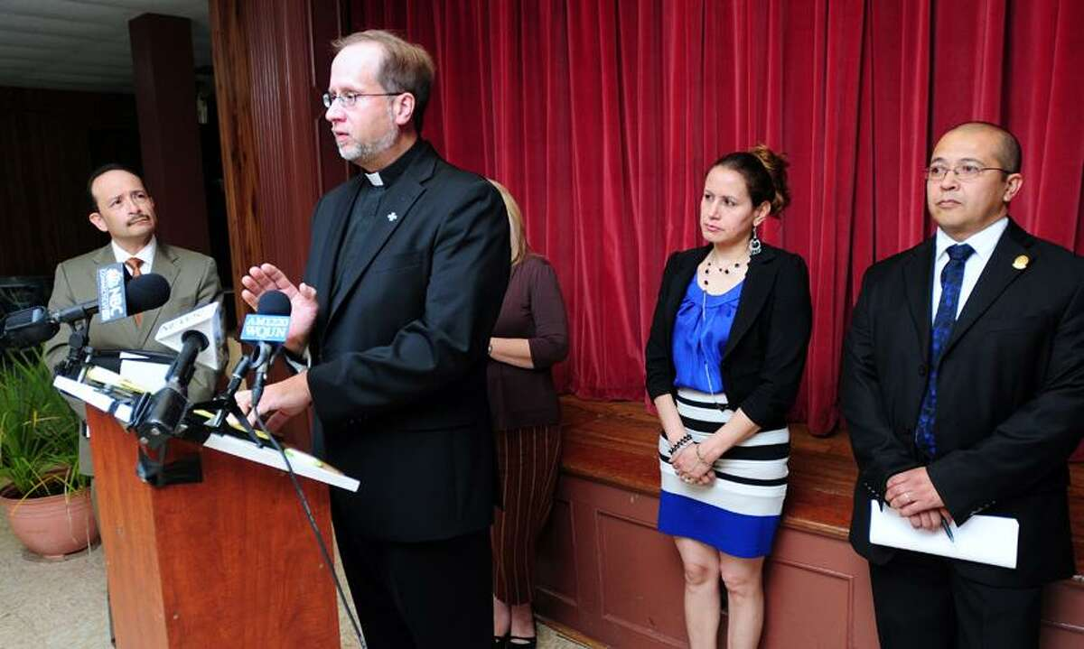 The Rev. James Manship (at podium) speaks at a press conference at St. Rose of Lima Church in New Haven concerning East Haven's agreement with the Department of Justice. Listening to Manship are Angel Fernandez-Chavero (left) of the St. Rose of Lima Pastoral Council, Marcia Chacon (right), owner of My Country Store in East Haven, and Maximo Romero of St. Lima of Rose Church. Photo by Arnold Gold/New Haven Register