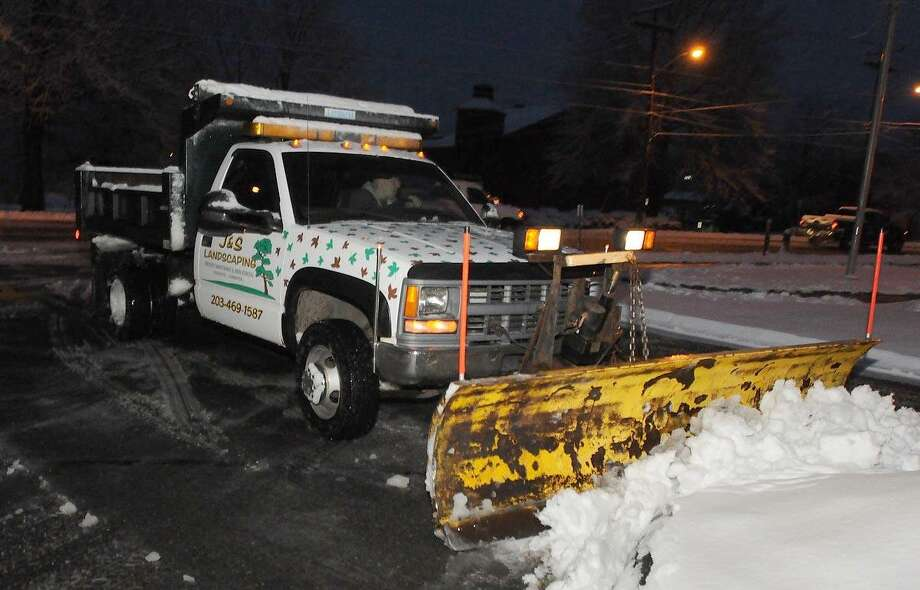John Kozlowski of East Haven and co-owner of J & S Landscaping plows out the Wells Fargo bank parking lot on the corner of Main Street and Laurel Street in Branford Friday. Kozlowski said that for him, the snow was unexpected. (Photo by Peter Hvizdak/New Haven Register) Photo: New Haven Register / ©Peter Hvizdak /  New Haven Register