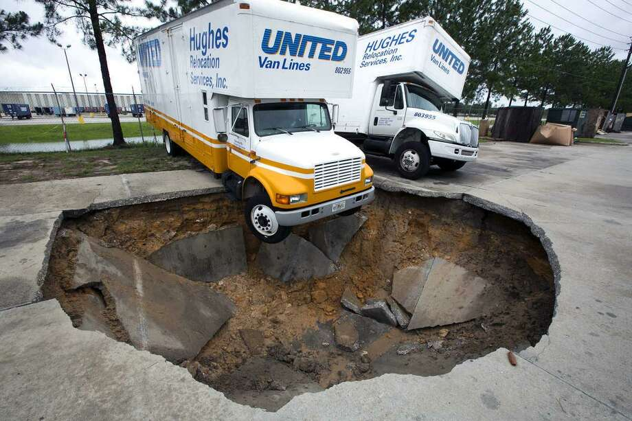 A truck hangs over the edge of a sinkhole that opened up in the parking lot of Hughes Relocation Services, Monday, June 25, 2012, in Salt Springs, Fla. Tropical Storm Debby raked the Tampa Bay area with high wind and heavy rain Monday in a drenching that could top 2 feet over the next few days and trigger widespread flooding. (AP Photo/The Ocala Star-Banner, Alan Youngblood) Photo: ASSOCIATED PRESS / AP2012