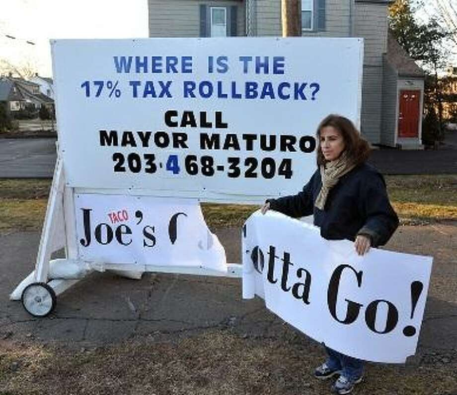 """In this file photo: Attorney Patricia Cofrancesco stands with a vandalized sign outside her law office that had read """"Taco Joe's Gotta Go!"""" in reference to Mayor Joe Maturo Jr. Cofrancesco was is her office when she witnessed two men get out of a red truck and one kicked holes in the sign. She ran out to get the license plate on the vehicle. The whole thing was caught on a new security system Cofrancesco had installed just two weeks ago. Peter Casolino/Register"""