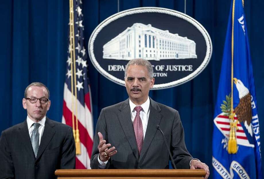 Attorney General Eric Holder speaks during a news conference at the Justice Department in Washington, Wednesday, Dec. 19, 2012, during an announcement that the international investment bank UBS Securities Japan Co. Ltd., will pay more than $1.5 billion in penalties in three nations to resolve charges of trying to manipulate an interest rate used as a benchmark in global banking transactions. Holder says UBS Securities Japan Co. Ltd., will plead guilty to felony wire fraud and admit to attempting to manipulate the London Interbank Offered Rate. Two former UBS senior traders will be charged with conspiracy, including one also charged with wire fraud in New York federal court. (AP Photo/Jose Luis Magana) Photo: AP / FR159526 AP