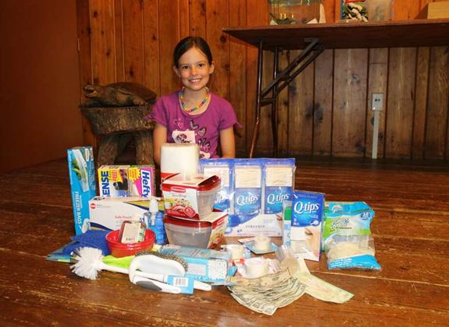 Macie Carter grins up from the birthday gifts she received for her eighth birthday. Macie asked her friends to donate items to the Roaring Brook Nature Center instead of giving her presents. (Photo courtesy Amy Carter)
