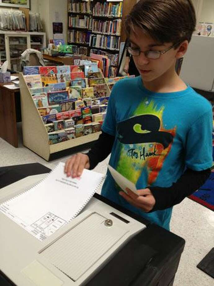 SARAH BOGUES/Register Citizen A student files his ballot during Tuesday's mock election in Barkhamsted.