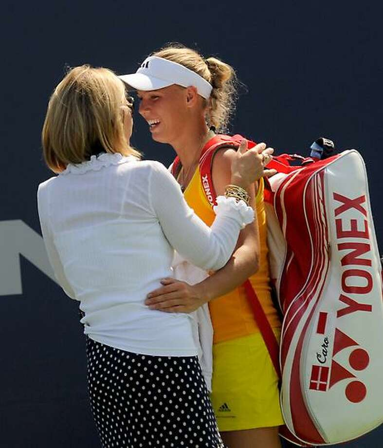 Tournament Director Anne Worcester, left, embraces Caroline Wozniacki as Wozniacki left the court after she won her quarterfinal match at the New Haven Open in New Haven, Conn., Thursday, Aug. 23, 2012. Wozniacki injured her kneeduring the match, but finished it, defeatng Dominika Cibulkova.  (Bob Child Photo) Photo: New Haven Register / Bob Child