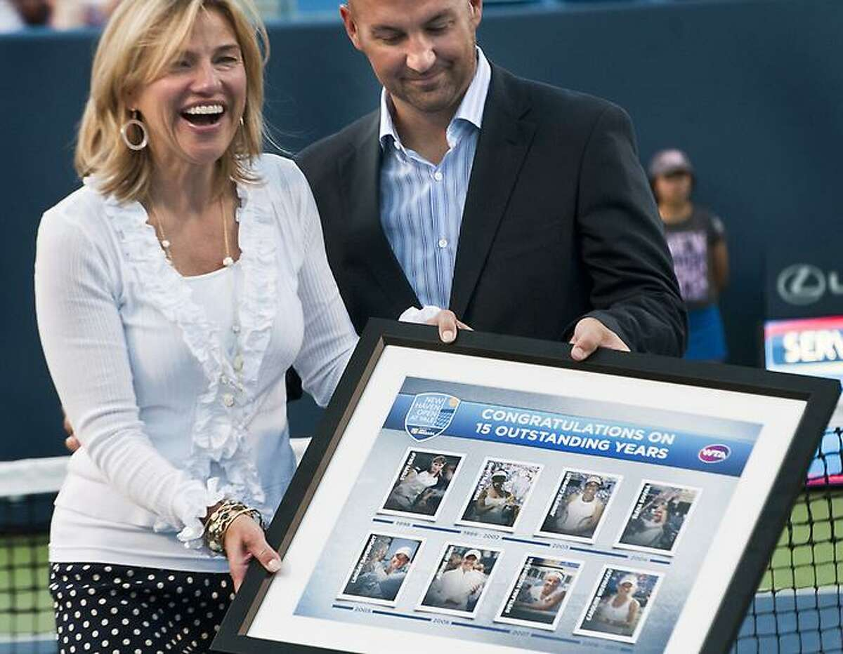 New Haven Open--Anne Worcester (L) reacts to the award presented to her by Lawrence Applebaum of the World Tennis Assoc. The award features fifteen years of women's tennis. Melanie Stengel/Register