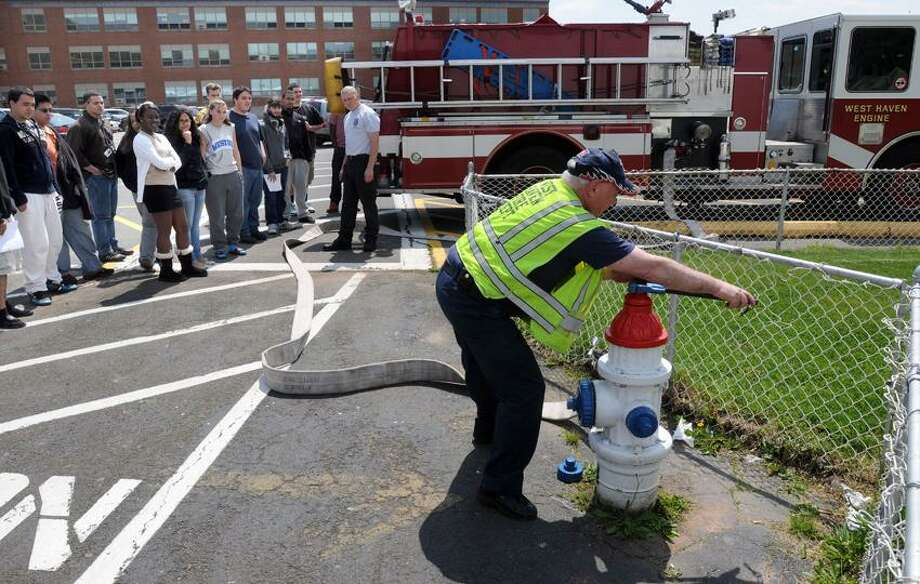 West Haven High School students participating in a fire academy class got to try out fire hoses with the assistance of the West Haven Fire Department Firefighter Roy Sebas, second from right, who is their teacher for the class and pump operator Firefighter Lee DeCarlo, right. Mara Lavitt/New Haven Register