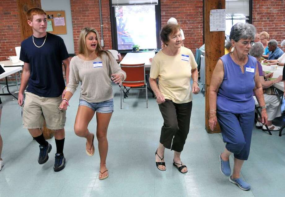 Ansonia High School students, Louis Nicoletti and Rita Gavin, line-dance with seniors Delores Smith, right, 74, of Shelton and Bianca Racan, 75, of Derby at the Ansonia Senior Center. The Ansonia High School Human Relations club and the seniors were enjoying the 3rd annual Ice Cream Social.  Nicoletti is a junior and Gavin is a senior.   Peter Casolino/New Haven Register