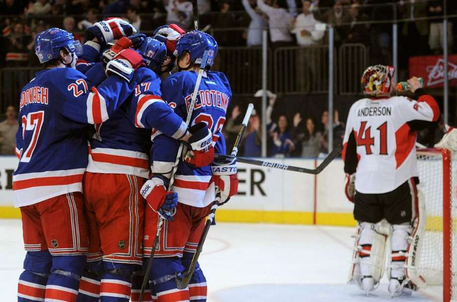 New York Rangers' Dan Girardi is congratulated by his teammates after scoring on Ottawa Senators goalie Craig Anderson (R) during the sceond period in Game 7 of their NHL Eastern Conference quarter-final playoff hockey game in New York, April 26, 2012. REUTERS/Ray Stubblebine (UNITED STATES  - Tags: SPORT ICE HOCKEY) Photo: REUTERS / X00272