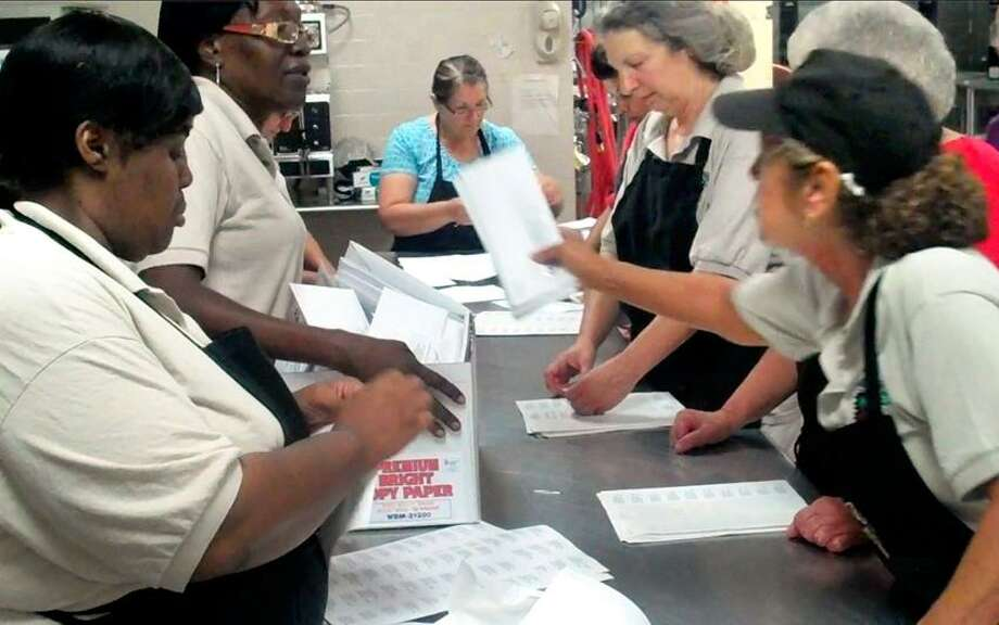 New Haven Food Service Department Cafeteria workers of local 217 paste labels, fold letters, and stuff 20k envelopes of school lunch applications at NHPS Central Kitchen at 75 Barnes Ave. on Thursday.