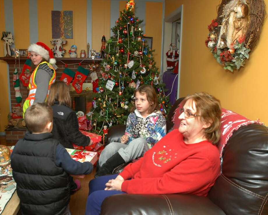"Catherine Avalone/The Middletown PressVolunteers from the community delivered Christmas presents to ten needy families as part of the Adopt-A-Family ""Spirit of Giving"" Annual Holiday Program sponsored by the Middletown Fire Department, South Fire District, Middletown Police Department and the Middletown Elks Lodge #771 Friday night."