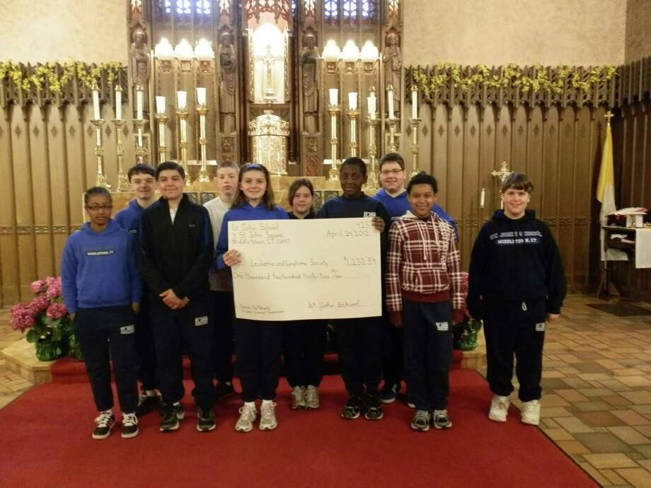 """St. John School Student Council holding a facsimile check for the money the school collected for """"Pennies for Patients"""" recently."""
