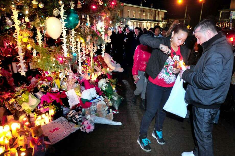 Elsa Castillo (right) and Angel Velez (far right) of Waterbury light a candle at a makeshift memorial for the victims of the Sandy Hook Elementary School shootings in the center of Sandy Hook on 12/17/2012.Photo by Arnold Gold/New Haven Register