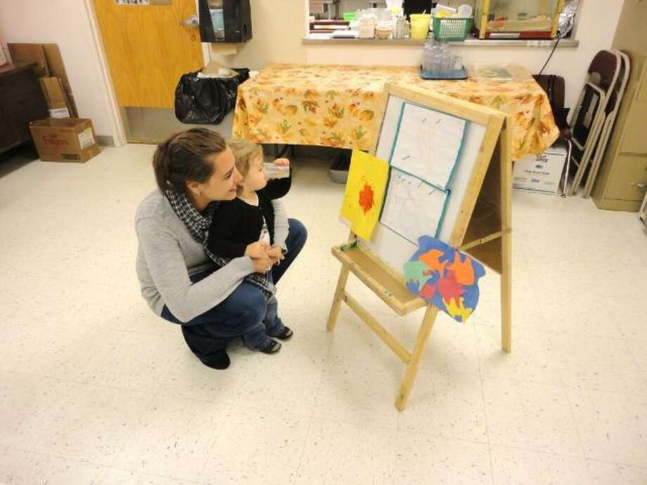 JASON SIEDZIK/ Register Citizen The Winsted Area Child Care Center took part in recognizing the Week of the Young Child, showcasing the art created by their over 100 infants and toddlers. Paige Corey, the center's executive director, looks at some of the art with her daughter, Lila.