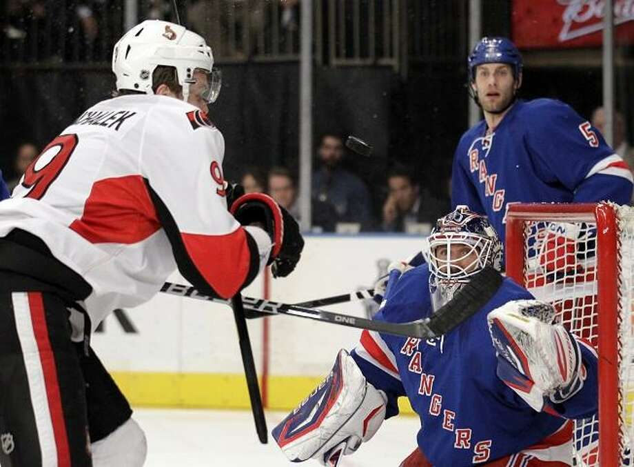 New York Rangers goalie Henrik Lundqvist, bottom right, of Sweden, and Ottawa Senators' Milan Michalek, left, of the Czech Republic, compete for the puck as it goes up in the air in front of the net during the first period of Game 7 of a first-round NHL hockey Stanley Cup playoff series on Thursday, April 26, 2012, in New York. Rangers' Dan Girardi (5) looks on.  (AP Photo/Julio Cortez) Photo: ASSOCIATED PRESS / AP2012